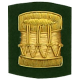 Hand Embroidered gold wire on green cloth drum insignia badge
