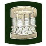Embroidered silver wire on green cloth drum insignia badge