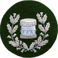 Embroidered silver wire on green cloth wreathed drum Drum Major insignia badge
